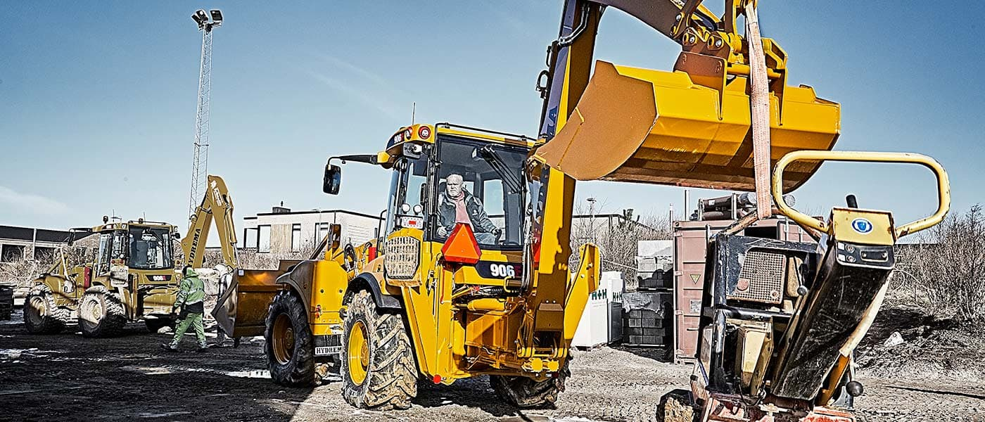 Hydrema 906F backhoe loader lifting a ramming machine