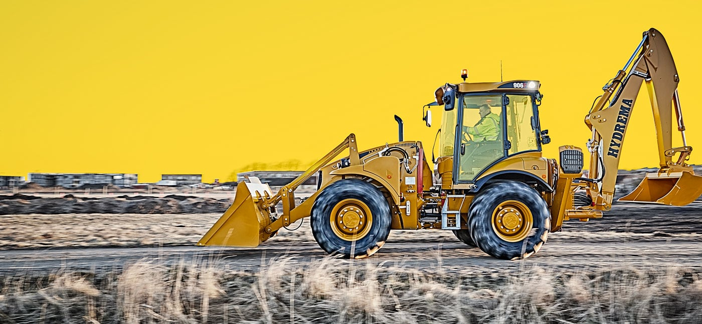Hydrema 906F backhoe loader in trnasport mode driving on a gravel road