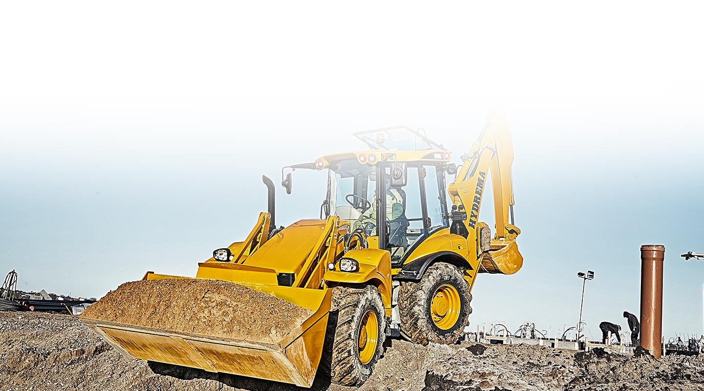 Hydrema 906F backhoe loader driving in rought terrain with a full bucket