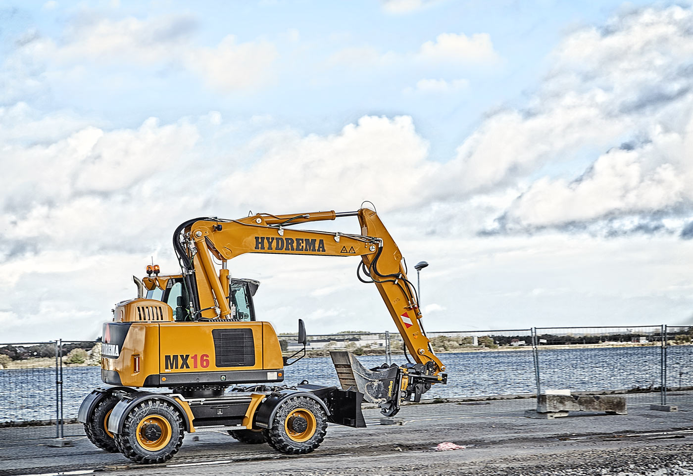 Hydrema MX16 Excavator mounted with Engcon tiltrotator driving along a harbor