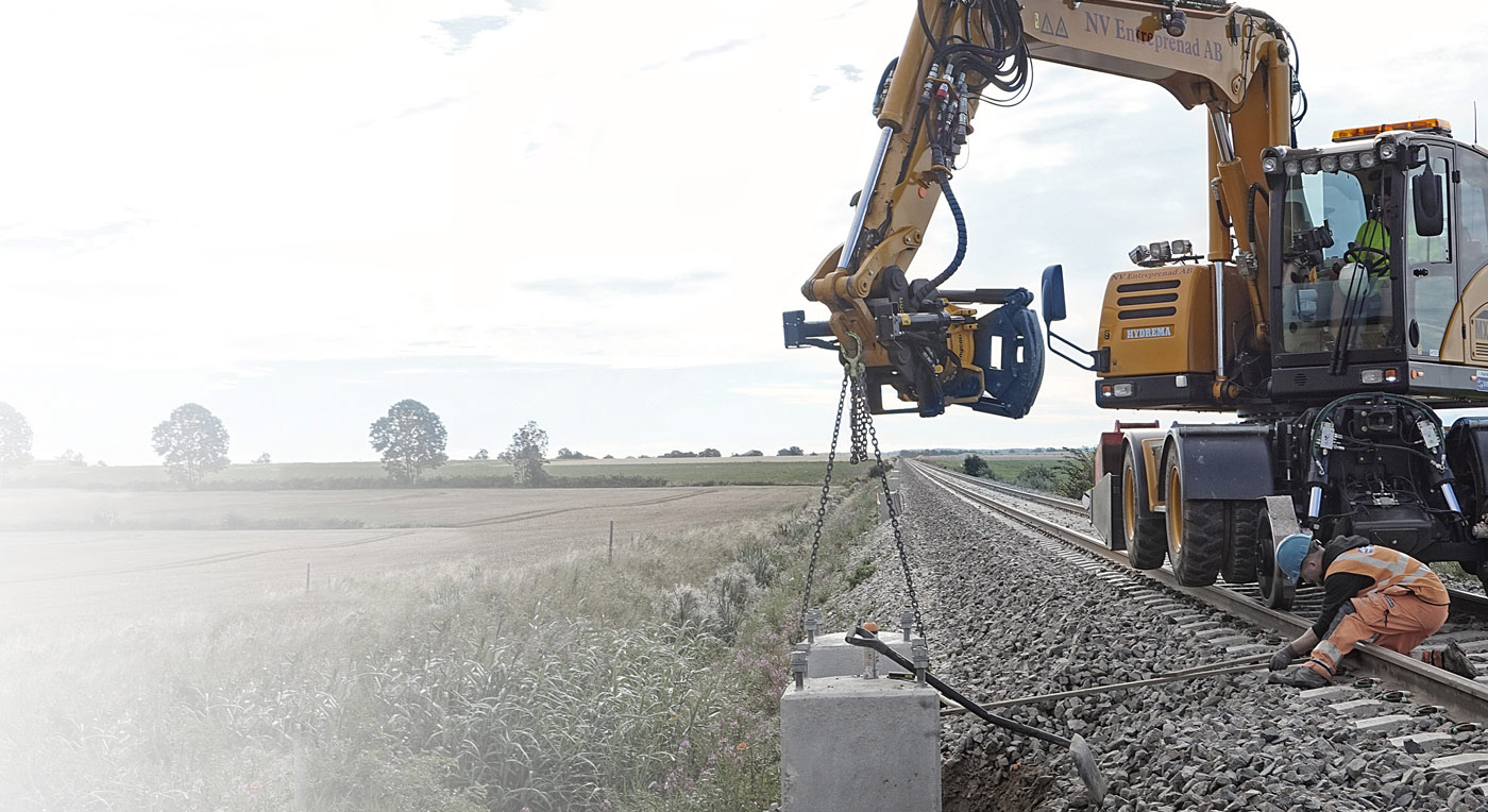 Hydrema mx20 rail lifting concrete near the railway track